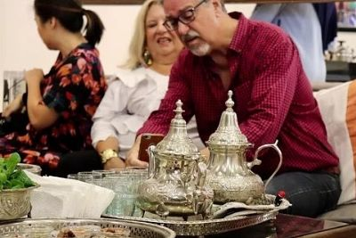 Two Moroccan Teapots On Tray In Front of Three Persons
