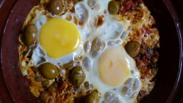 Two Cracked Eggs Cooked In Tomato Sauce With Peas And Olives